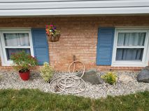 Red bricks, blue shutters, garden hose and stones. And rocks royalty free stock photo