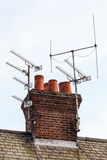 Red bricks chimney and TV antennas Royalty Free Stock Images