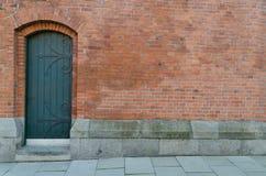 Red bricks door. Old door in a building Royalty Free Stock Images