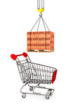 Red Bricks over wooden Pallet with Supermarket Shopping Cart Stock Photos