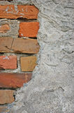 Red bricks stone wall background closeup, cracked ruined stucco Stock Photo