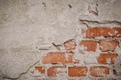 Red brickwork underneath concrete wall. Textured suface. Half painted wall. Background. Cracks and roughness stock photo