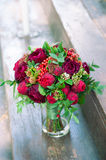 Red bridal boquet. Bridal bouquet with red flowers and berries standing in a glass vase Royalty Free Stock Images