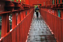 Red bridge. Man walking by a red iron bridge. industrial style. in a dimmed day, after rain. in Buenos Aires Argentina Royalty Free Stock Images