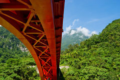 Red bridge across mountains. Red steel arch bridge across mountains. Mountains full of green forest Stock Photo