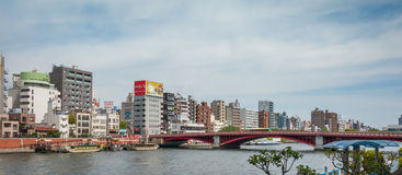 The red bridge across Sumida river to Asakusa Business area. Tokyo, Japan - May 4, 2017: The red bridge across Sumida river to Asakusa Business area Royalty Free Stock Image