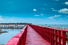 Red bridge and bamboo line. Slow down wave prevent coastal erosion Royalty Free Stock Photography