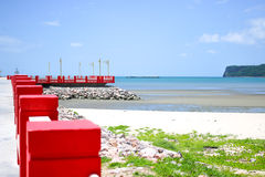 Red bridge and beach. The bridge extends to the sea with blue sky Stock Photos