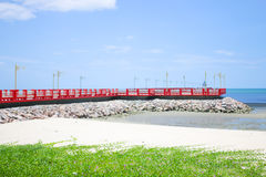 Red bridge on the beach. The bridge extends to the sea with blue sky Royalty Free Stock Photo