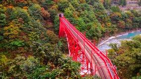 Red bridge cross the river. Shin Yamabiko red bridge cross the river at Unazuki station in Kurobe gorge Stock Photo