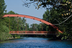 Red Bridge Extending Over the River Stock Photo