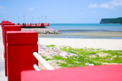 Red bridge foreground. The bridge extends to the sea with blue sky Stock Photo