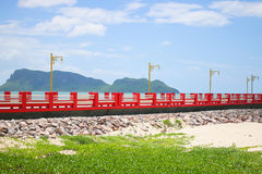 Red bridge go to sea. The bridge extends to the sea with blue sky Royalty Free Stock Image