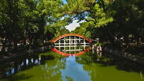 Red bridge and its reflect. In a garden of Osaka, Japan stock photo