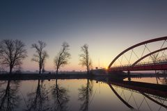 Red bridge over the Bosut river in Vinkovci, Croatia. Modern bridge. The sun goes up behind the new bridge over the Bosut River in Vinkovci, Croatia stock photo