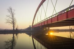 Red bridge over the Bosut river in Vinkovci, Croatia. Modern bridge. The sun goes up behind the new bridge over the Bosut River in Vinkovci, Croatia stock photos