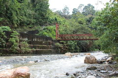 A red bridge over a swollen, rushing river on a misty day in the hills of Batatal. Royalty Free Stock Photo