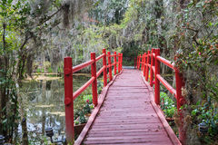 Red Bridge Pedestrian Crossing Southern Garden SC. Pedestrian red bridge connects trails surrounding a lake through a garden of hanging moss covered trees and stock image