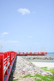 Red bridge on the rock as vertical. The bridge extends to the sea with blue sky Royalty Free Stock Photos