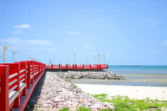 Red bridge on the rock. The bridge extends to the sea with blue sky Stock Photo