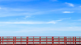 Red wood bridge in the sea. With clear and bright blue sky in background Royalty Free Stock Image