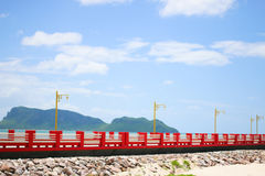 Red bridge and the sky. The bridge extends to the sea with blue sky Stock Photography