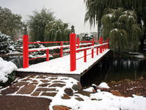 Red bridge and snow falling in Japanese garden Stock Photo