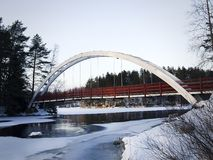 A red bridge with a white arch above a stream. A red bridge with a white arch above a an icy stream during Finnish Spring. It`s called `The bridge of Love Stock Images