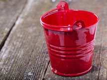 Red brilliant metal bucket on old gray boards Royalty Free Stock Image