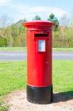 Red British mailbox. Red British pillar mailbox in rural Suffolk, England Stock Image