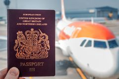 A red British passport held up against a background of a generic plane on a bright sunny day stock photos