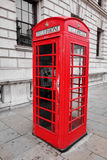 Red British phone booth. Street scene with a British phone box in London Royalty Free Stock Photography