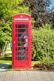 Red British Phone Booth. Red British telephone booth in town of Mount-Royal,Quebec, Canada Stock Photo