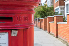 Red British Post Box. Traditional British post box against blurry terrace house background stock images