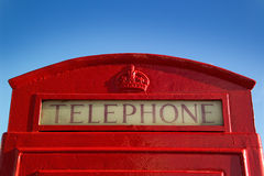 Red British public telephone kiosk. Detail, set against a clear blue sky Royalty Free Stock Photos