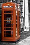 Red British telephone booth. Two iconic red British telephone booths on an urban street with coin-operated payphones for public convenience Stock Photography
