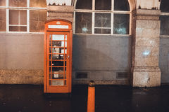 Red British Telephone Booth on a city street. Alongside a commercial building with arched windows, with copy space in a travel and communication concept Stock Photos