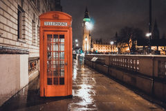 Red British Telephone Booth in London. Near the Houses of Parliament and Big Ben illuminated on a wet cold night Stock Image