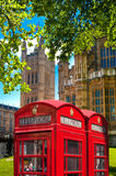 Red British telephone box in front of Parliament tower, London Stock Photography