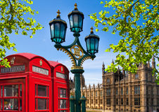 Red British telephone box in front of Parliament tower, London Stock Photo