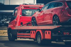 Broken Car on a Towing Truck. Red Broken Car on a Red Towing Truck. Closeup Photo. Vehicle Mechanical Problem on the Road stock photos