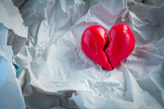 Red broken heart closeup on crump paper.jpg Royalty Free Stock Image
