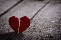 Red broken heart. On wooden background - dark and moody royalty free stock photography