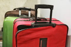 Red broken traveling luggage, crack and torn at the corner with other baggage in background, at the airport. Need to be repaired and claimed the airline Stock Image