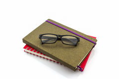 Red and brown book with glasses. Stock Photos