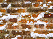 Red brown brick wall covered with snowflakes royalty free stock images