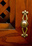 Red and brown cupboard wood door. Cupboard wood door. Focus on old-fashioned doorhandle royalty free stock photography