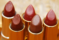 Red and brown lipsticks. Close-up on golden background Royalty Free Stock Images