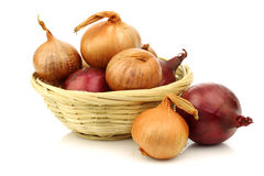 Red and brown onions in a wicker basket Royalty Free Stock Photos