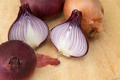 Red and brown onions on a wooden cutting board. Some onions are cut into half stock photos